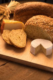 Bread and cheese. On chopping board and rustic background Royalty Free Stock Images
