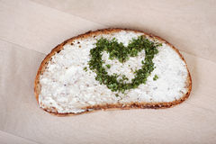 Bread With Cheese Cream Spread And Heart Made Of Herbs. Slice of bread with cheese cream spread and heart made of herbs on wooden table Stock Images