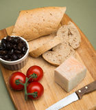 Bread and cheese/Delicious organic cream milk cheese, olives and home-made bread and ripe tomatoes on wooden board. Royalty Free Stock Image