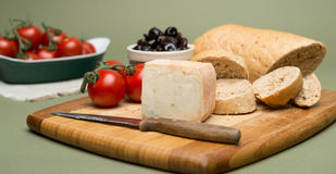 Bread and cheese/Delicious organic cream milk cheese, olives and home-made bread and ripe tomatoes on wooden board. Royalty Free Stock Photo