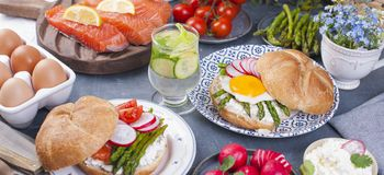 Bread with cheese, egg and asparagus, another bread with salmon and. asparagus. Healthy food. Tasty breakfast. Gray background. Banner, copy space Stock Image