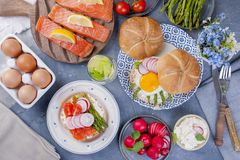 Bread with cheese, egg and asparagus, another bread with salmon and. asparagus. Healthy food. Tasty breakfast. Gray background.  Stock Image