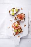 Bread, cheese and ham and grapes Stock Photos