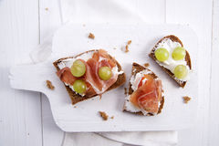 Bread, cheese and ham and grapes Stock Images