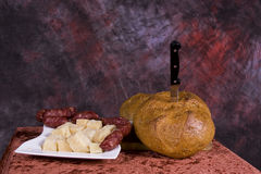 Bread and cheese platter. A loaf of freshly baked bread and a platter of diced cheese on a dark purplish background Royalty Free Stock Images