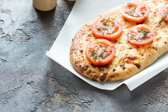 Bread with cheese and red tomatoes, green spices. Pizza with cheese and tomatoes on a concrete background Royalty Free Stock Photos