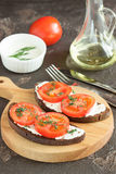 Bread with cheese, tomatoes and herbs on a wooden board. Sandwich with soft cheese and tomatoes on dark bread Royalty Free Stock Photography