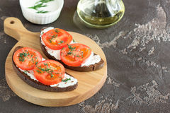 Bread with cheese and tomatoes on a wooden board. Sandwich with soft cheese and tomatoes on dark bread Stock Photos
