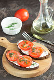 Bread with cheese and tomatoes on a wooden board in the snack. Sandwich with soft cheese and tomatoes on dark bread Stock Photos