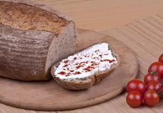 Bread and cherry tomatoes. Closeup of freshly baked, hot, loaf of bread with cream cheese and ripe cherry tomatoes Stock Image