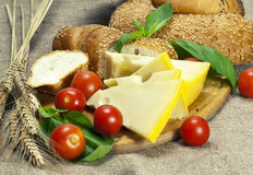 Bread, cherry tomatoes, cheese and basil on wooden cutting board. Bread, cherry tomatoes, cheese and basil leafs on wooden cutting board. Sack background Royalty Free Stock Photo
