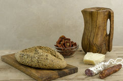Bread, chesee, chorizo and olive wooden cutting board and pitcher. Royalty Free Stock Photo