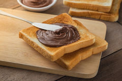 Bread with chocolate cream on wooden plate Stock Photos