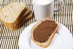 Bread with chocolate spread milk and hazelnuts. Bread with chocolate and a glass of milk Stock Photos