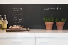 Bread On Chopping Board With Shopping List On Blackboard Stock Images