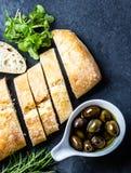 Bread ciabatta, arugula, olives, rosemary on stone slate black background. Top view stock image