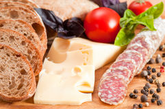 Bread ciabatta, salami, cheese, tomato and basil. Italian bread ciabatta, salami, cheese, tomato and basil. Focus on foreground Stock Photo