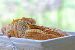 Bread. Close up of loafs and slices of authentic bread in a basket. Focus on slices, shallow dof Royalty Free Stock Images