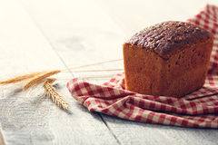 Bread on a cloth with spikelets of wheat on a wooden boards Stock Images