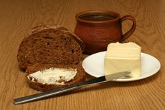 Bread and coffee. Bread, coffee and butter on the wooden table royalty free stock images