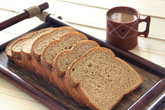 Bread and coffee on a wooden table. Tray of bread with coffee placed on a patio table Stock Images