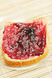 Bread with cowberry jam on mat Stock Image