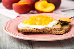 Bread with creamcheese and stewed yellow fruits. 2 pieces of bread with creamcheese and stewed yellow fruits royalty free stock image