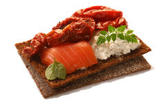 Bread crisp with salmon, soft cheese, dried tomatoes and chervil Royalty Free Stock Photos