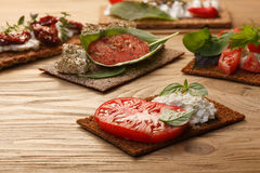Bread crisp with tomato, cheese and basil. Bread crisp (crispbread open-faced sandwich) with heirloom tomato, cream cheese and fresh basil leaves on wooden table stock photos