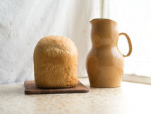 Bread with a crispy crust on a stand near the window in the countryside Royalty Free Stock Image