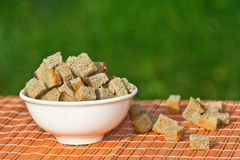 Bread croutons in a white сup. On a green background Stock Photography