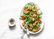 Bread crumbs deep fried chicken, arugula, cherry tomatoes tapas salad on a light background, top view. Delicious  snack, royalty free stock image