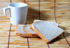 Bread and cup on bamboo plate. Many slice of bread from whole wheat flour and white cup on bamboo plate stock photo
