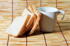 Bread and cup on bamboo plate,. Many slice of bread from whole wheat flour and white cup on bamboo plate royalty free stock photos