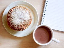 Bread, a cup of cocoa and notebook. Royalty Free Stock Images