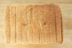 Bread cut. Stack of sliced whole wheat bread on isolated wood background Stock Photos
