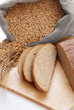 Bread cut on a board and a bag with wheat Royalty Free Stock Image
