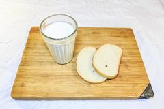 Bread cut into pieces on a wooden board next to a glass of milk stock photo