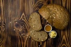 The bread and cut the slices and a cup of honey and butter lying on a wooden background. Top view Royalty Free Stock Photos