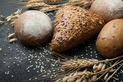 Bread of different kinds on a dark board with spikelets of wheat, rye and oats. Carbohydrates and diet.  stock image