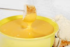 Bread dipped in cheese fondue Stock Images