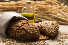 Bread, ears and grains on sackcloth. RRye bread in a paper bag, ears, a glass bottle with vegetable oil and grain on sackcloth Stock Photo