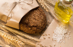 Bread, ears, grains and vegetable oil on sackcloth. Rye bread in a paper bag, ears, a glass bottle with vegetable oil, salt and grain on sackcloth Stock Photos