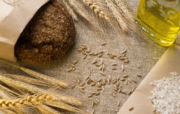 Bread, ears, grains and vegetable oil on sackcloth. Rye bread in a paper bag, ears, a glass bottle with vegetable oil, salt and grain on sackcloth Stock Photo