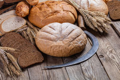 Bread, ears and sickle on old boards Stock Photo