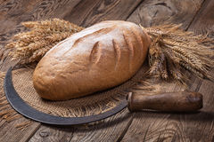 Bread, ears and sickle on old boards Royalty Free Stock Photo