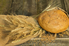 Bread with ears and wheat grain closeup on a  wooden background Royalty Free Stock Photos