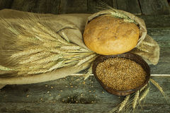 Bread with ears and wheat grain on a rough cloth Stock Photos