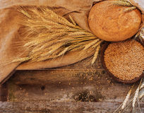 Bread with ears and wheat grain  on a wooden background Royalty Free Stock Photography