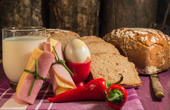 Bread, egg, milk and vegetables. Breakfast. The composition of the food products on the table Stock Photography